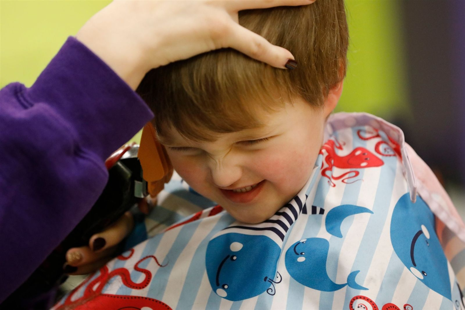 """Reid Baldwin, 3, of Lockport, reacts to the """"tickle"""" from the clippers as he gets a trim at Shear Madness in Orchard Park, which specializes in children's haircuts, Saturday, Feb. 10, 2018."""