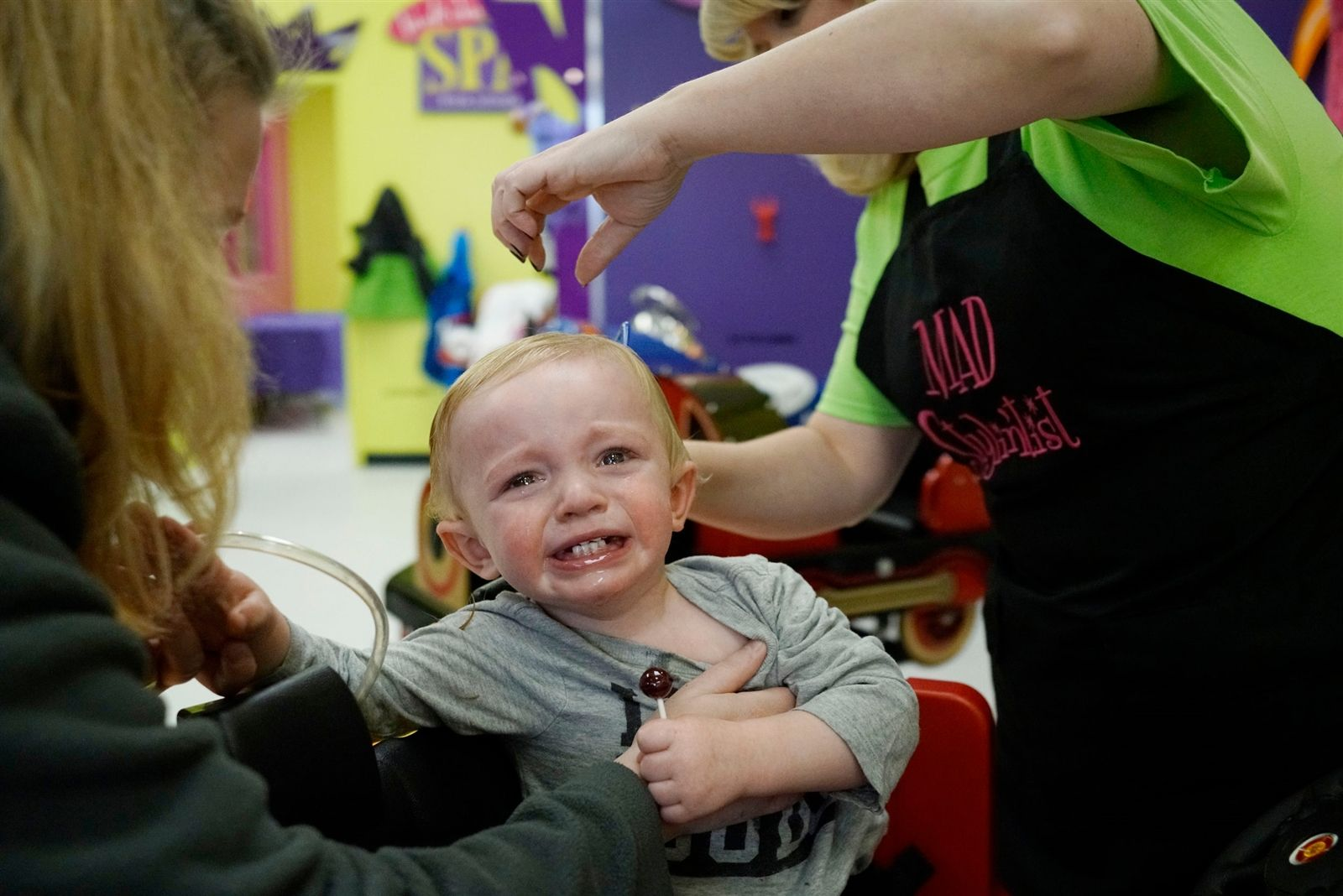 Ashley Deinzer tries to keep her 18-month-old son Chase calm and hold him still as Nikki Flynn gives him a cut at Shear Madness in Orchard Park, which specializes in children's haircuts, Saturday, Feb. 10, 2018.