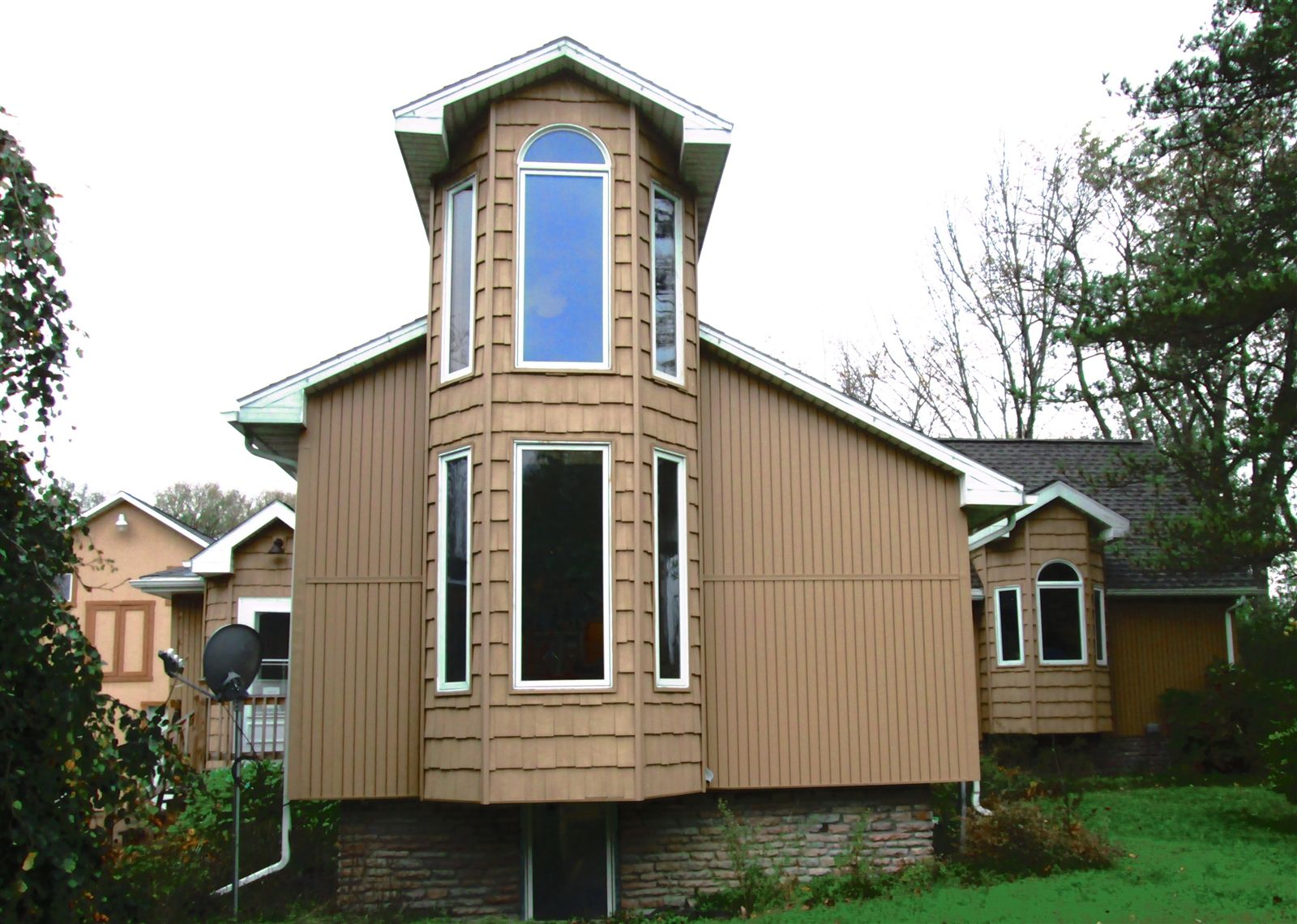 The exterior of the house,  with a view of the clerestory with stacked windows. The couple added the vinyl siding a couple of years ago.