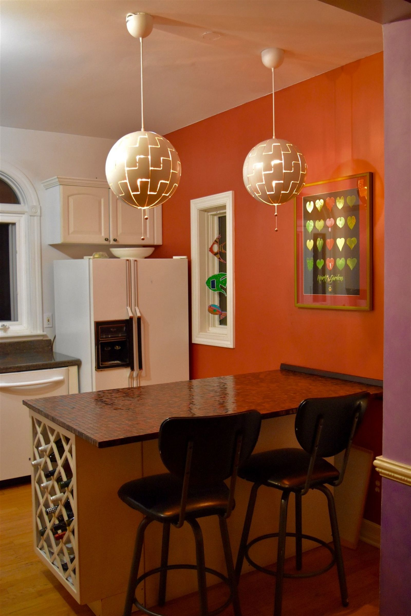 Jim Charlier built the kitchen island and tile countertop and also designed the poster on the wall. The pendants are from Ikea. The feature color wall is Ralph Lauren Persimmon Gold Metallic. Daughter Margaux made the metal fish hanging in the window.
