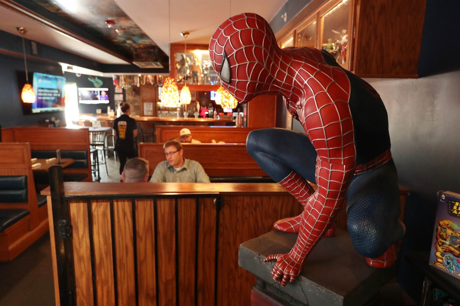 A life-size Spider-Man statue is crouched and ready as diners have lunch.