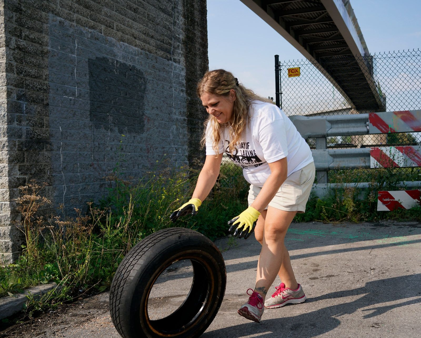 Rachel Poss of Ingram Micro rolls away a discarded tire while helping with a beautification project at the Hudson Street pedestrian bridge.