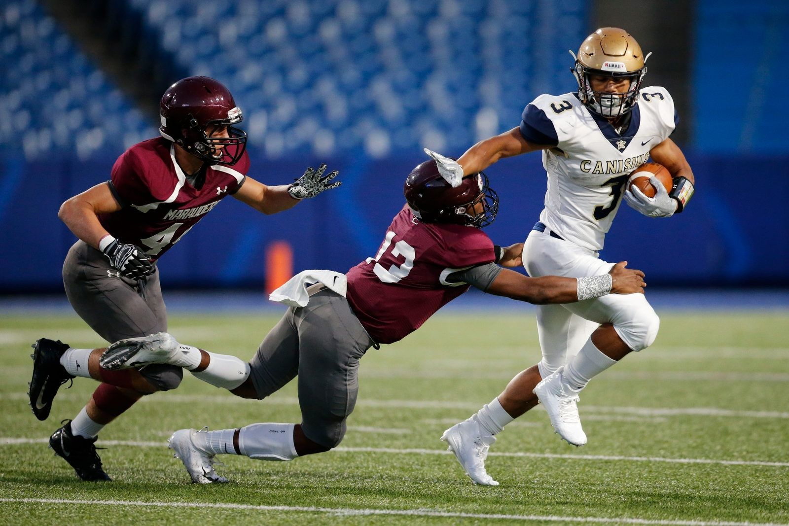 Canisius running back Joel Nicholas looks for extra yards as St. Joe's Micah Brown gets an hand on him during the first quarter.