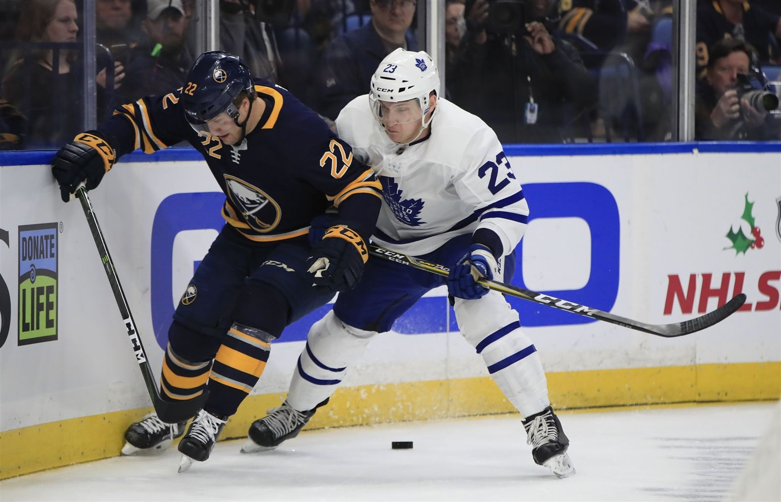 Buffalo Sabres center Johan Larsson and Toronto Maple Leafs Travis Dermott battle for a loose puck during first period action at the KeyBank Center on Tuesday, Dec. 4, 2018.