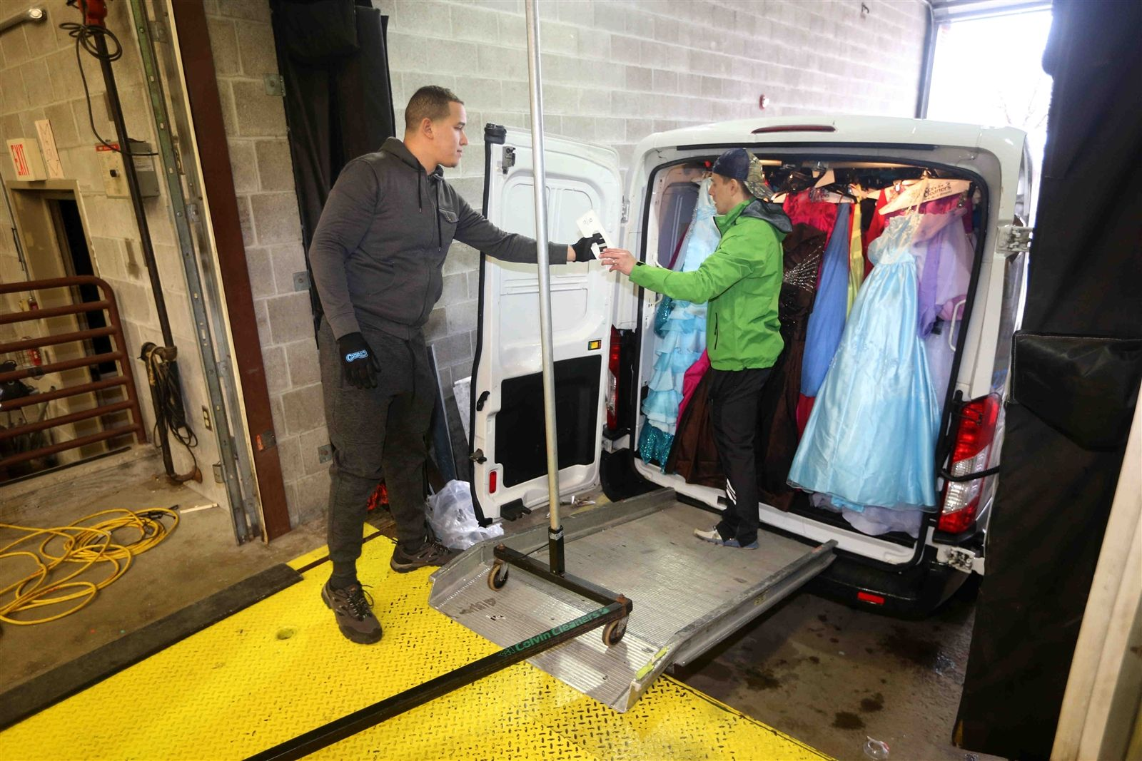 Plinio Calcano and Chris Billoni from Colvin Cleaners unload gowns from a truck at Shea's.