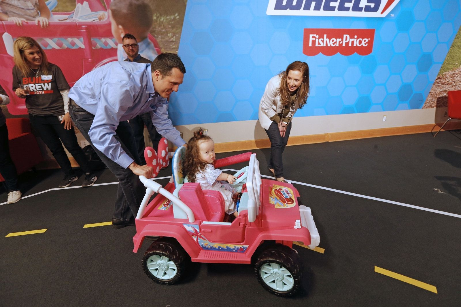 Scott and Alicia Kocsis of Lancaster help their daughter Olivia, 2, with her first ride.