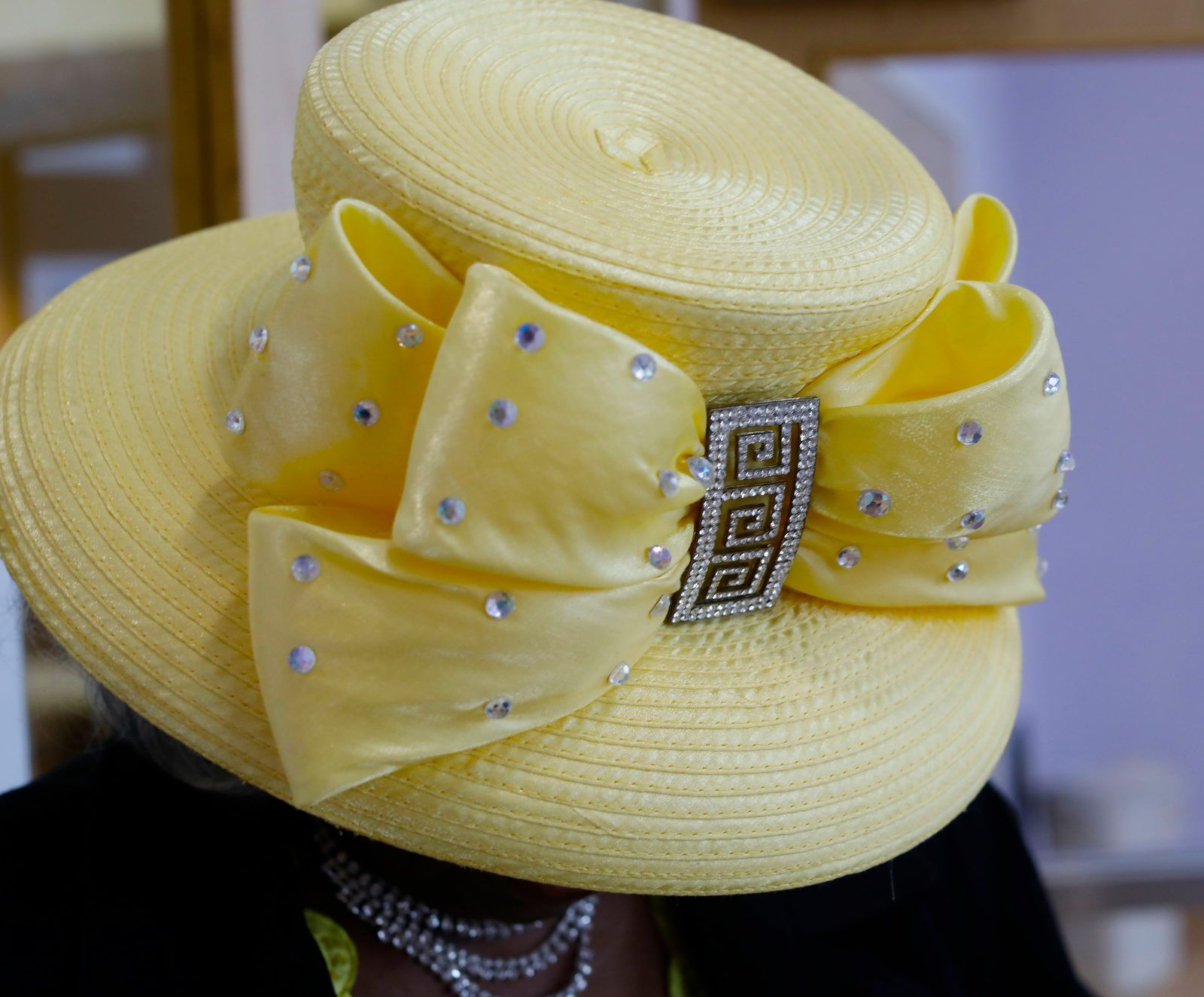 Mildred McDaniel wears a yellow hat with a gem-studded bow at Elim Christian Fellowship.