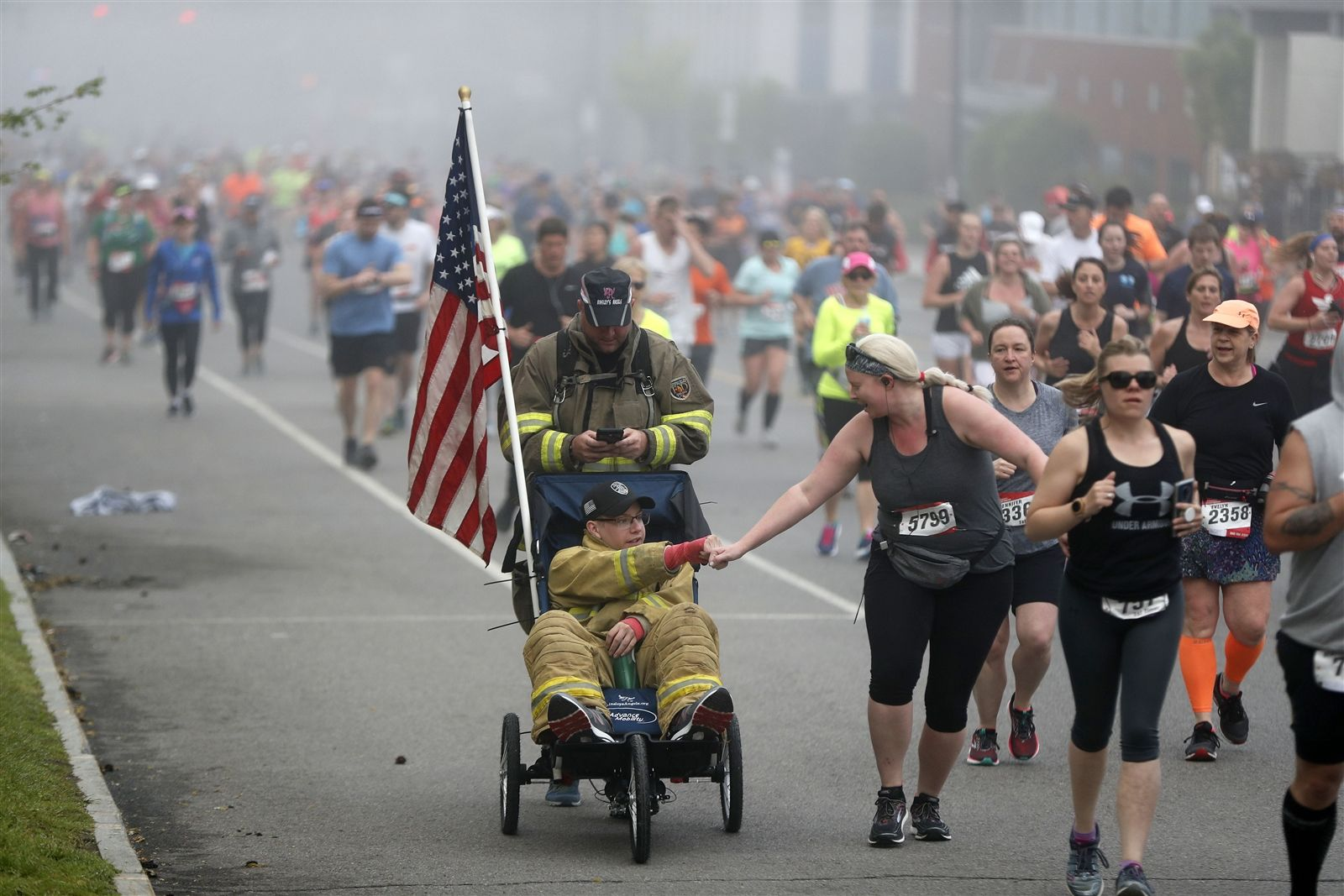 Firefighter Tim Richardson of Buffalo gets a fist bump from a runner as he's pushed by Ryan Mast, a firefighter from New Orleans, during the Buffalo Marathon Sunday, May 26, 2019.
