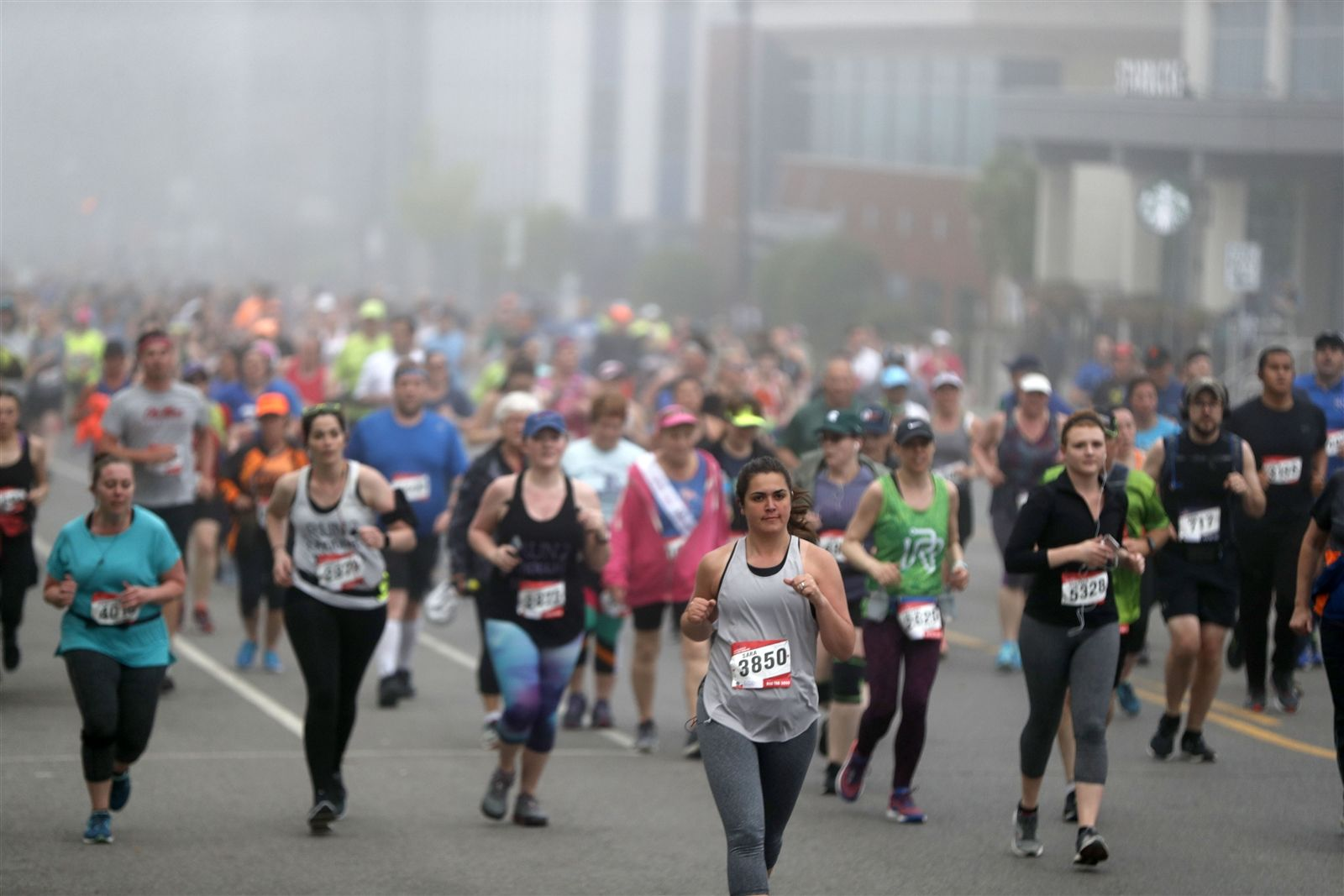 Runners take to Delaware Avenue in the fog during the Buffalo Marathon Sunday, May 26, 2019.