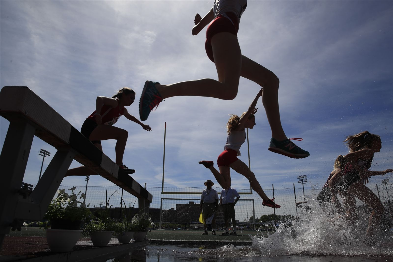 Girls jump over the water in Section 1 of the Girls 2000 Meter Steeplechase Championship at the NYSPHSAA Track & Field Championships at Middletown High School on Saturday, June 8, 2019.