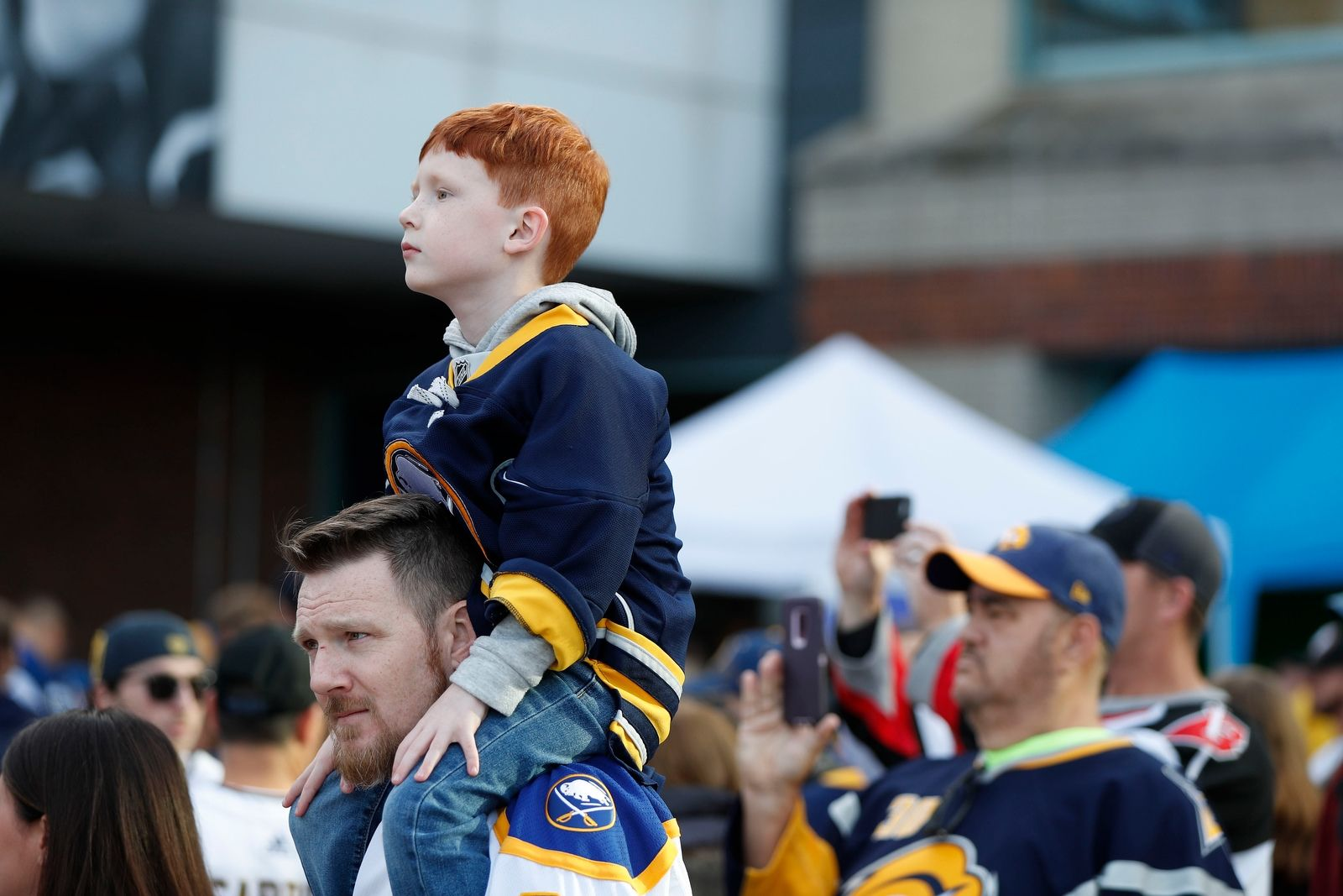 Tom Kanaley gives his son Thomas Kanaley a better view before the Buffalo Sabres Alumni Captains arrive on the Blue and Gold carpet for the season home opener at KeyBank Center in Buffalo Saturday, Oct. 5, 2019.