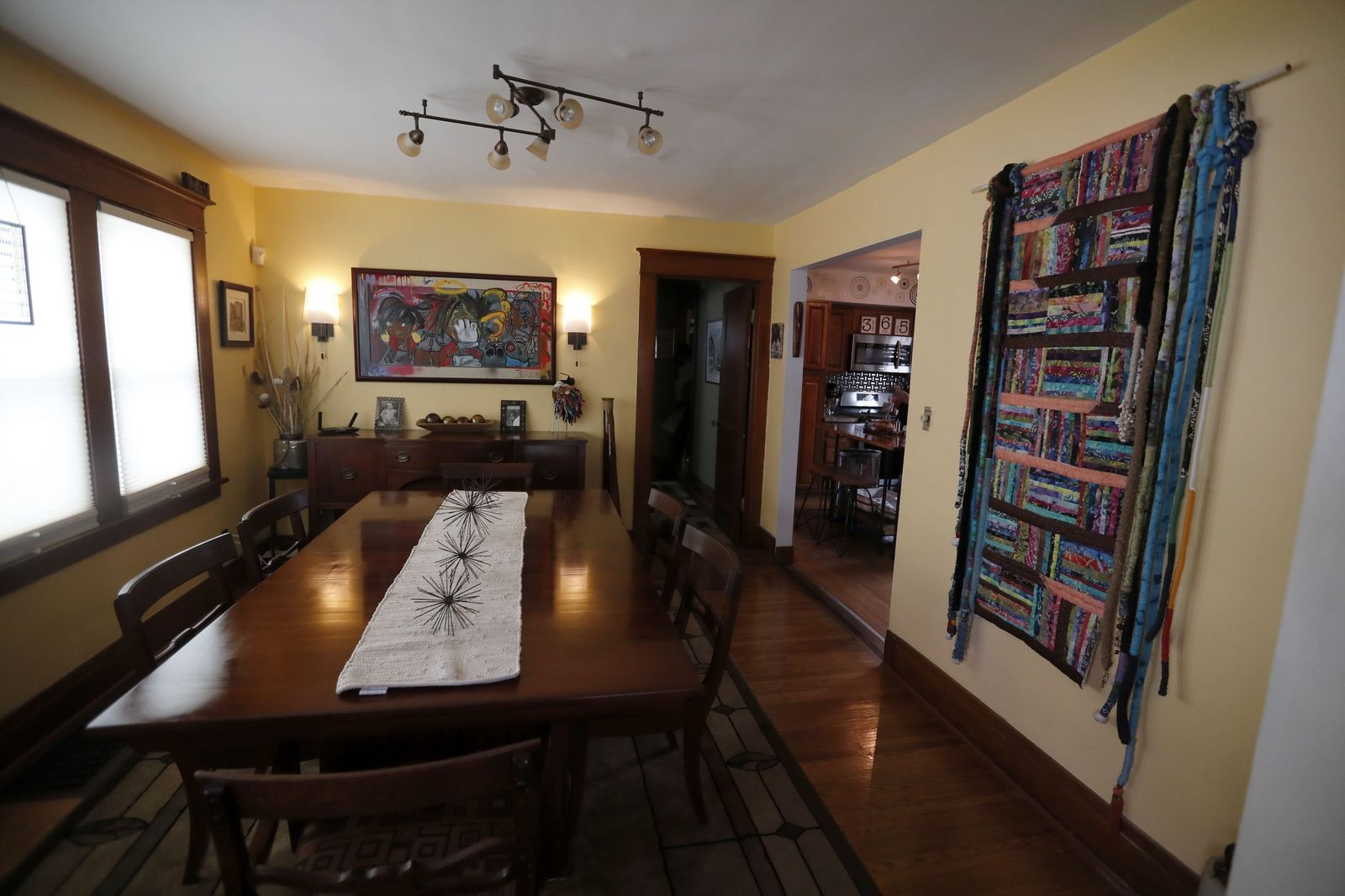 The dining room features a fabric wall hanging by Florida fiber artist Billie McCray and a painting above the buffet by Byron Brown Jr. The room is painted Melted Butter by BEHR.