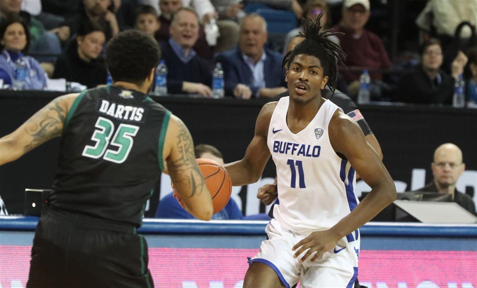 Buffalo Bulls forward Jeenathan Williams (11) dribbles the ball up the court against Ohio Bobcats guard Jordan Dartis (35) in the first half.