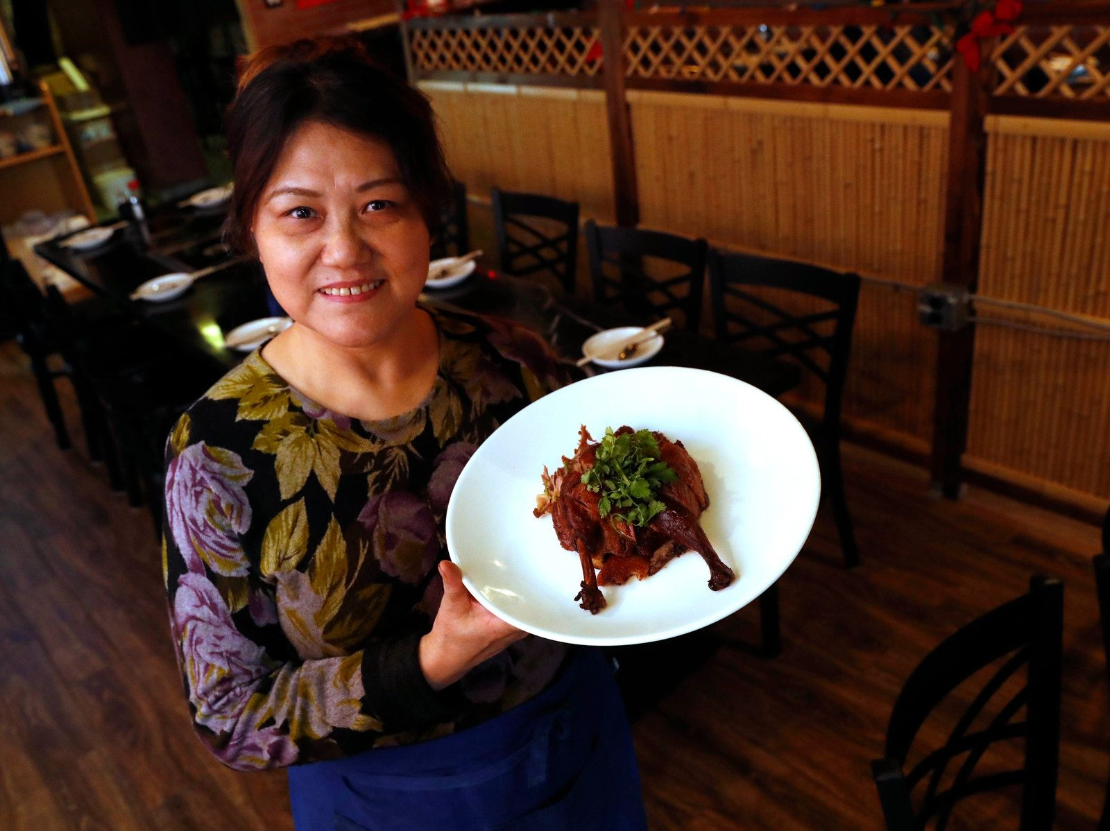 Owner and chef Xiuying Xu presents the smoked tea duck Sichuan style.
